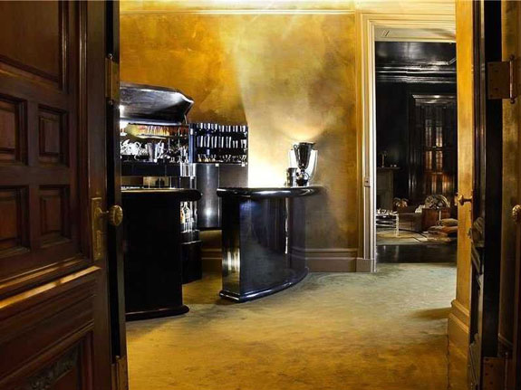 while-the-rest-of-the-interior-is-more-eclectic-this-chic-gold-room-with-a-polished-black-bar-is-pure-elegance