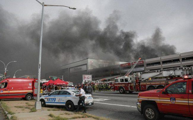 Vehicles catch fire in parking garage; firefighters injured